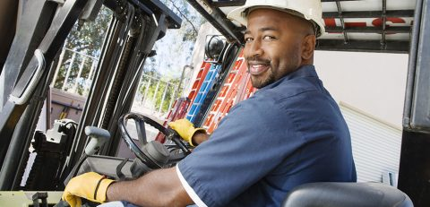 Portrait of a happy African American mature male worker driving forklift at workplace